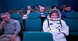 audience in planetarium show - one member is wearing an astronaut suit
