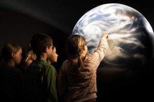 Students admiring large scale replica of planet earth inside planetarium
